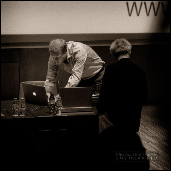 El arquitecto Mende se acerca para ayudar a Tapio Rosenius a resolver un pequeño problema informático durante su ponencia.
