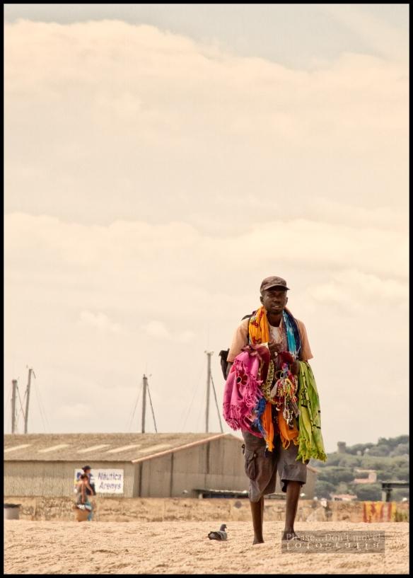 Un vendedor ambulante en la playa de Arenys de Mar en el Maresme (Cataluña). A pesar de que el día amenazaba con lluvia, y eramos pocos en la playa, estos hombres nunca dejaron de hacer su reiterativo paseo de ida y vuelta por la playa con la esperanza de vender cualquier cosa y justificar el día.